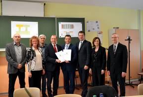 Oberbürgermeister Sven Wagner (4.v.l.) erhält den Fördermittelbescheid von Finanzminister André Schröder (5.v.l.). Über die bevorstehende Sanierung des Schulzentrums Nord freuen sich insbesondere die Leiterin der Gemeinschaftsschule