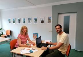 Kerstin Beckmann zeigt Sebastian Petsch eine Broschüre in Leichter Sprache mit Fragen und Antworten zum Budget für Arbeit. Diese und viele andere Infomaterialien erhalten Interessierte im Büro der Teilhabemanagerin.